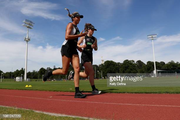 Erica Fowler and Katie Lynch of the Mapies run laps during a Collingwood Magpies AFLW and AFL team training session at the Holden Centre on December...