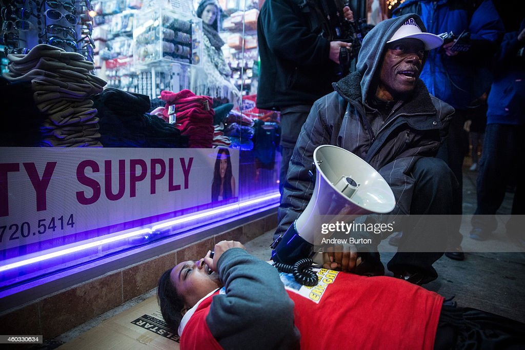 Erica Garner, daughter of Eric Garner, lays down in the spot where her father died during a die-in, alongside other people protesting the Staten Island, New York grand jury's decision not to indict a police officer involved in the chokehold death of Eric Garner in July, on December 11, 2014 in the Staten Island Neighborhood of New York City. Protests have continued throughout the country since the Grand Jury's decision was announced last week.