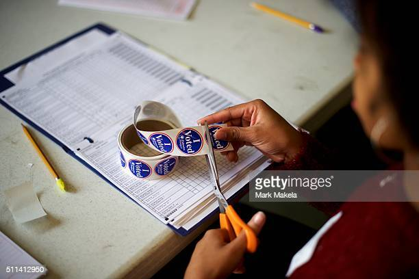 Erica Levine a poll manager at the Colleton County Fire Rescue polling precinct cuts 'I Voted' stickers on February 20 2016 in Walterboro South...