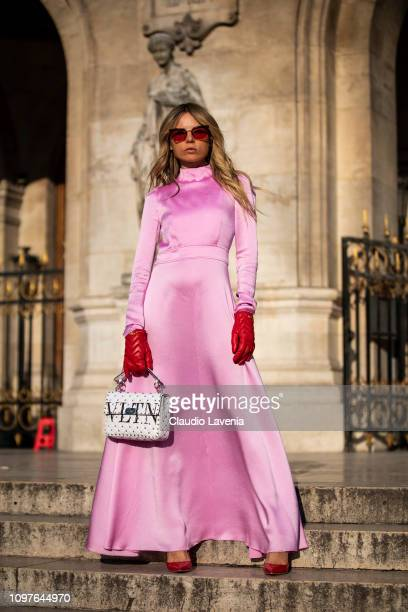 Erica Pelosini Leeman, wearing a long pink dress, red Gucci gloves, red heels and Valentino white bag, is seen outside Schiaparelli during Paris...