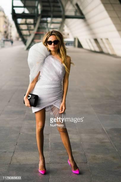 Erica Pelosini Leeman wearing a white decorated mini dress neon pink heels and black bag is seen on Day 8 Paris Fashion Week Autumn/Winter 2019/20 on...