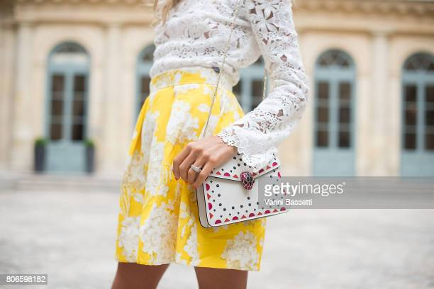 Erica Pelosini poses with a Bulgari bag after the Schiaparelli show at Place Vendome during Paris Fashion Week Haute Couture FW 17/18 on July 3, 2017...