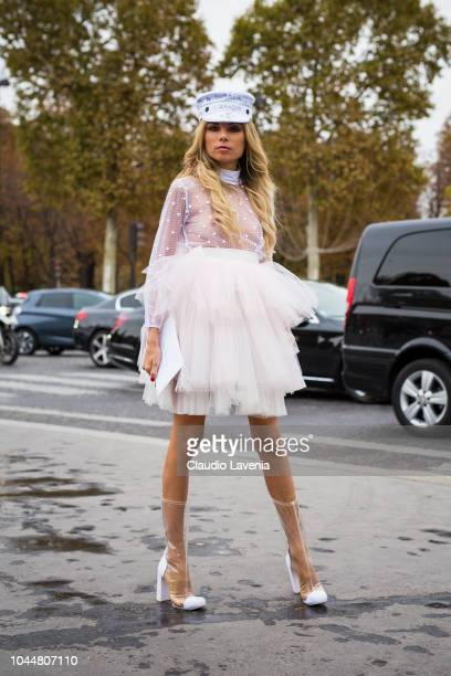 Erica Pelosini wearing a tulle mini dress seethrough boots and printed baker boy hat is seen before the Chanel show on October 2 2018 in Paris France