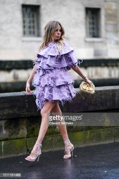 Erica Pelosini wears a purple ruffled fringed dress a golden Valentino bag high heeled shoes outside Valentino during Paris Fashion Week Womenswear...
