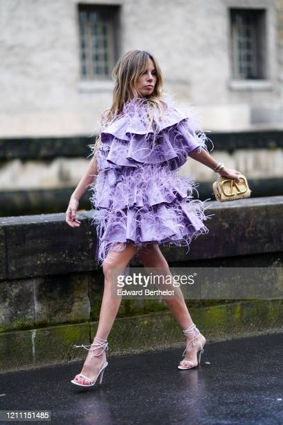 Erica Pelosini wears a purple ruffled fringed dress, a golden Valentino bag, high heeled shoes, outside Valentino, during Paris Fashion Week -...