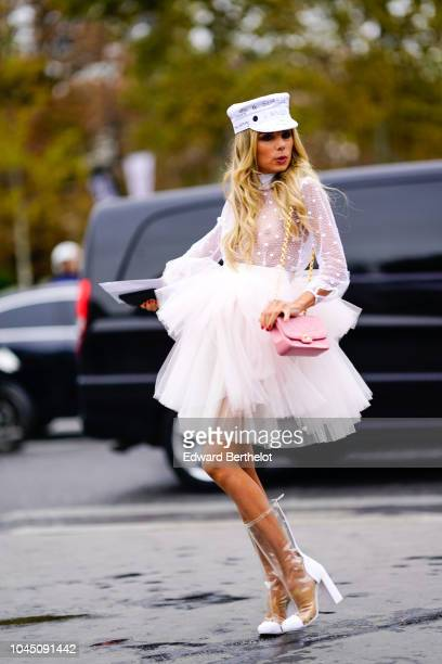 Erica Pelosini wears a white cap hat a pink Chanel bag a white lace mesh ruffle dress outside Chanel during Paris Fashion Week Womenswear...