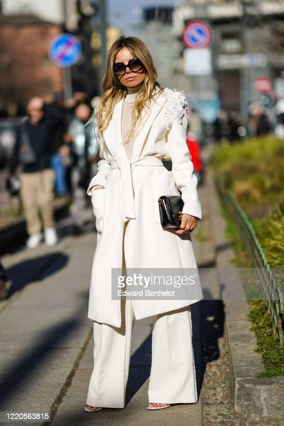 Erica Pelosini wears sunglasses, a white coat with fluffy parts on the shoulders, flare pants outside Max Mara, during Milan Fashion Week Fall/Winter...