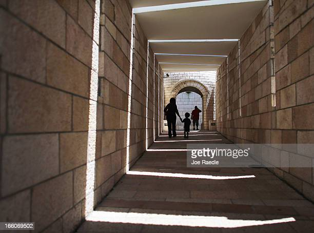 Erica Thompson and threeyearold George Thompson walk through the Holocaust Memorial during Yom HaShoahHolocaust Remembrance Day on April 8 2013 in...