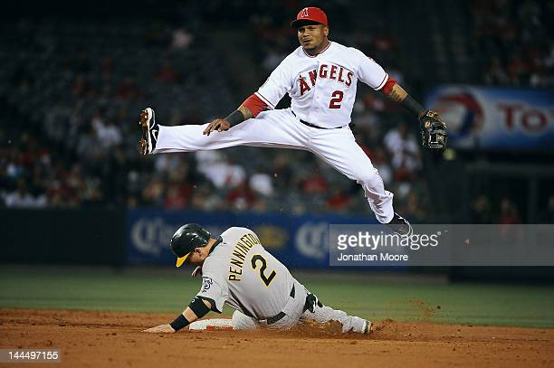Erick Aybar of the Angels of Anaheim turns a double play over Cliff Pennington of the Oakland Athletics in the third inning at Angel Stadium of...