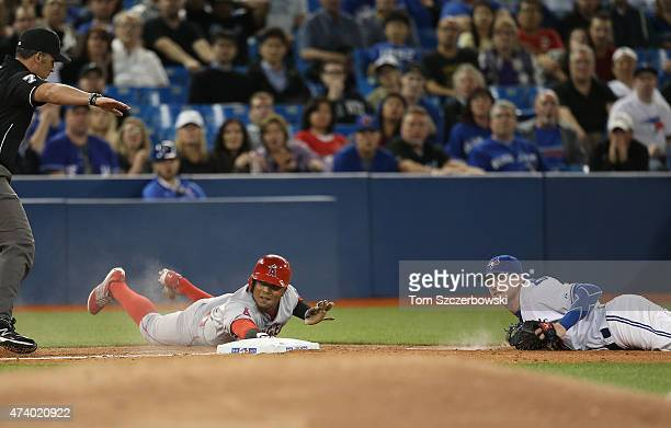Erick Aybar of the Los Angeles Angels of Anaheim evades the tag of Josh Donaldson of the Toronto Blue Jays to arrive safely at third base in the...