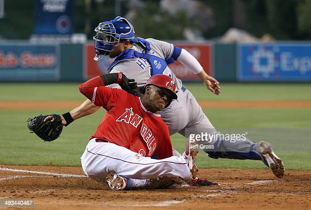 Erick Aybar of the Los Angeles Angels of Anaheim slides safely past the tag of catcher Brett Hayes of the Kansas City Royals and scores a run in the...