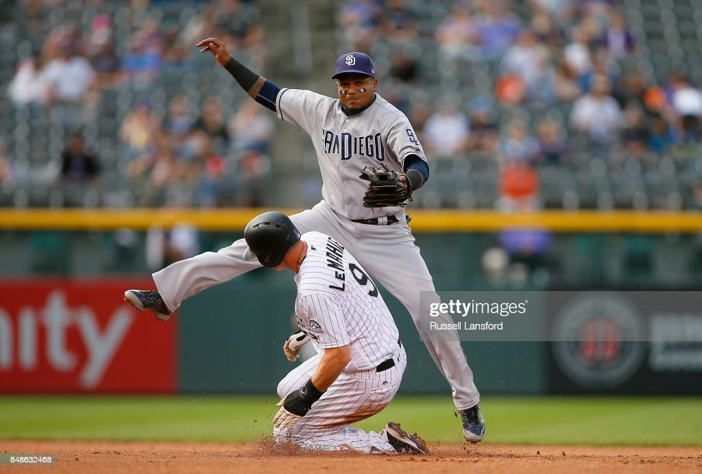 Erick Aybar #8 of the San Diego Padres attempts to turn a double play as DJ LeMahieu #9 of the Colorado Rockies slides into second base in the fifth inning of a regular season MLB game between the Colorado Rockies and the visiting San Diego Padres at Coors Field on September 17, 2017 in Denver, Colorado.