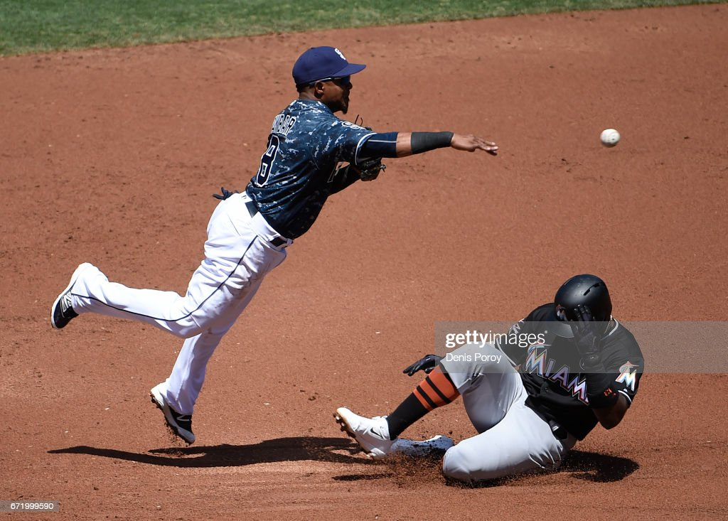 Erick Aybar #8 of the San Diego Padres leaps over Marcell Ozuna #13 of the Miami Marlins as he tries to turn a double play during the second inning of a baseball game at PETCO Park on April 23, 2017 in San Diego, California.