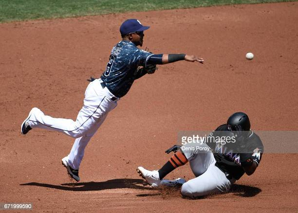Erick Aybar of the San Diego Padres leaps over Marcell Ozuna of the Miami Marlins as he tries to turn a double play during the second inning of a...