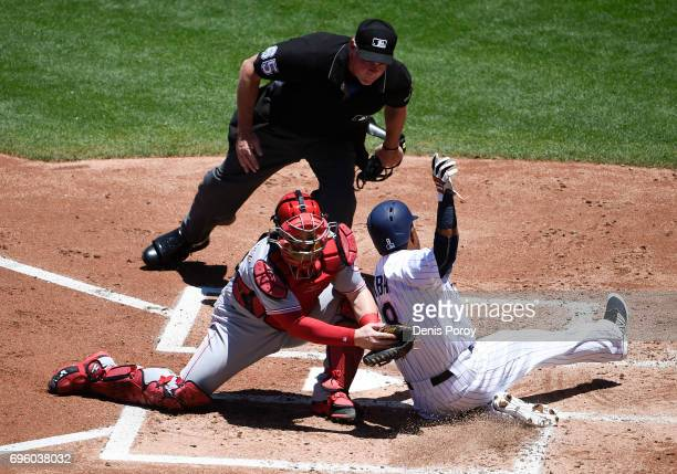 Erick Aybar of the San Diego Padres misses the plate as Tucker Barnhart of the Cincinnati Reds tries to tag him during the second inning of a...