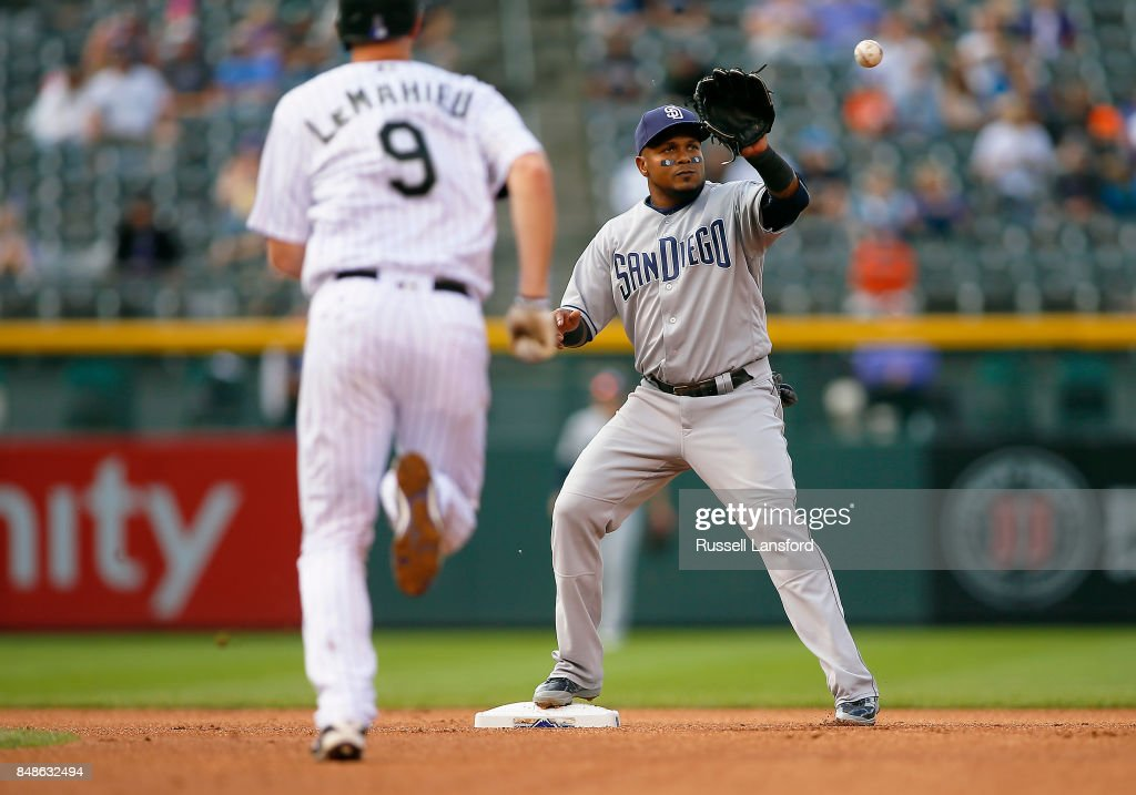 Erick Aybar #8 of the San Diego Padres receives a throw to get DJ LeMahieu #9 of the Colorado Rockies during the fifth inning of a regular season MLB game between the Colorado Rockies and the visiting San Diego Padres at Coors Field on September 17, 2017 in Denver, Colorado.