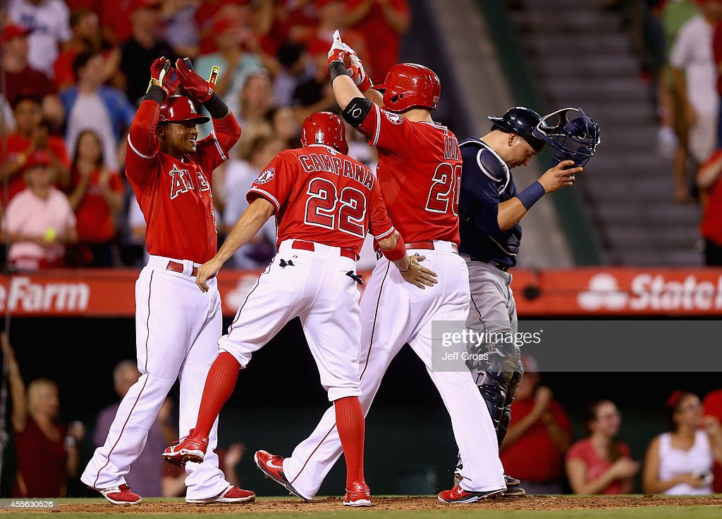Erick Aybar #2, Tony Campana #22 and C.J. Cron #20 of the Los Angeles Angels of Anaheim celebrate Cron's three-run home run in the seventh inning, as Seattle Mariners catcher Jesus Sucre #2 looks down at Angel Stadium of Anaheim on September 17, 2014 in Anaheim, California.