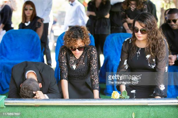 Erick Bubu LoboPerez Ariela LoboPerez and Jennifer Turcios kneel during the graveside service for their brother Aris Eduardo LoboPerez at Fairview...