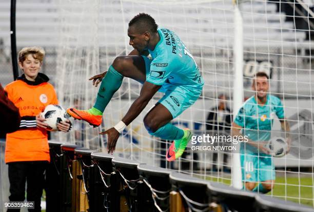 Erick Castillo from Barcelona SC of Ecuador hops over a fence to celebrate with teammates after scoring a goal against Brazilian club Fluminense...