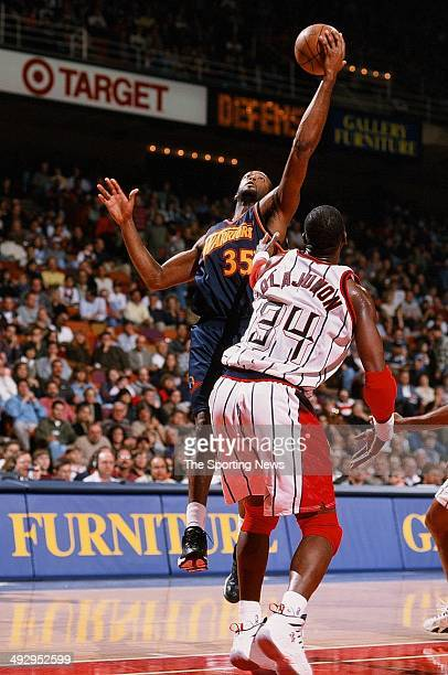 Erick Dampier of the Golden State Warriors lays the ball up over Hakeem Olajuwon of the Houston Rockets during the game on November 22 1997 at the...