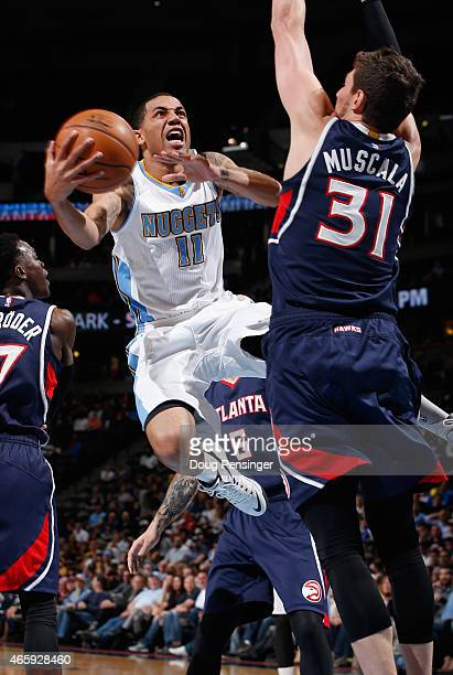 Erick Green of the Denver Nuggets lays up a shot against Mike Muscala of the Atlanta Hawks at Pepsi Center on March 11 2015 in Denver Colorado The...