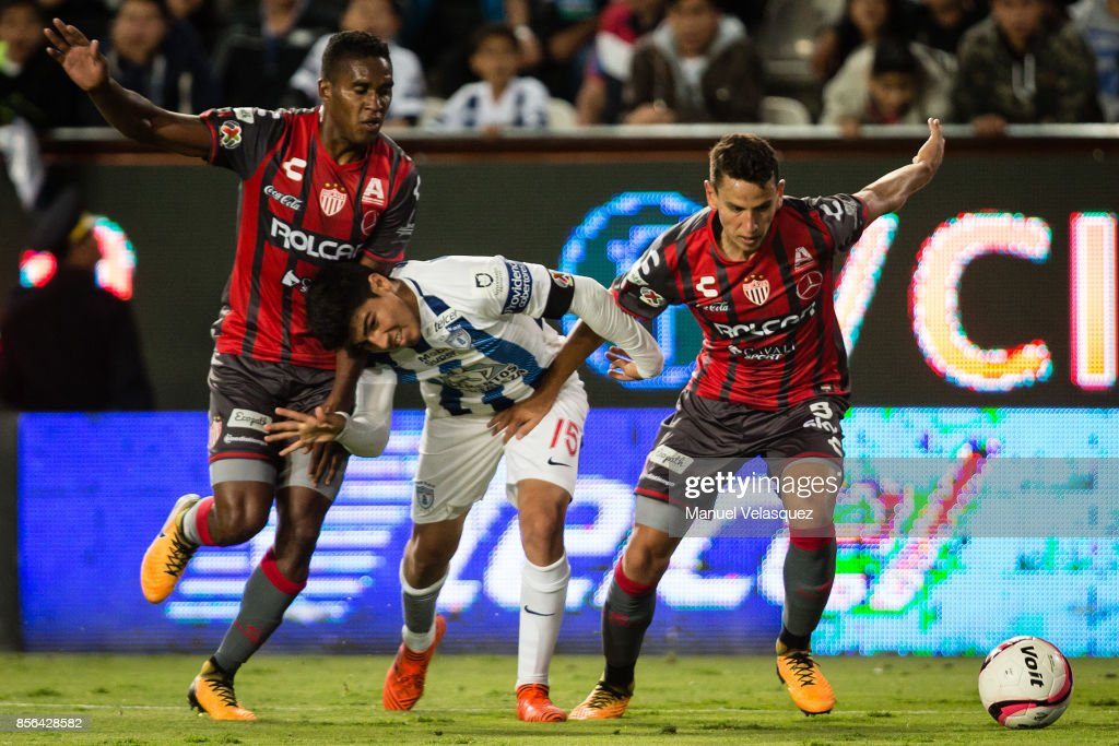 Erick Gutierrez (C) of Pachuca struggles for the ball with Brayan Beckeles (L) and Igor Lichnovsky (R) of Necaxa during the 12th round match between Pachuca and Necaxa as part of the Torneo Apertura 2017 Liga MX at Hidalgo Stadium on September 30, 2017 in Pachuca, Mexico.