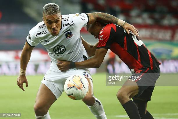 Erick of Athletico Paranaense fights for the ball with Javier Parraguez of ColoColo during a group C match of Copa CONMEBOL Libertadores 2020 between...
