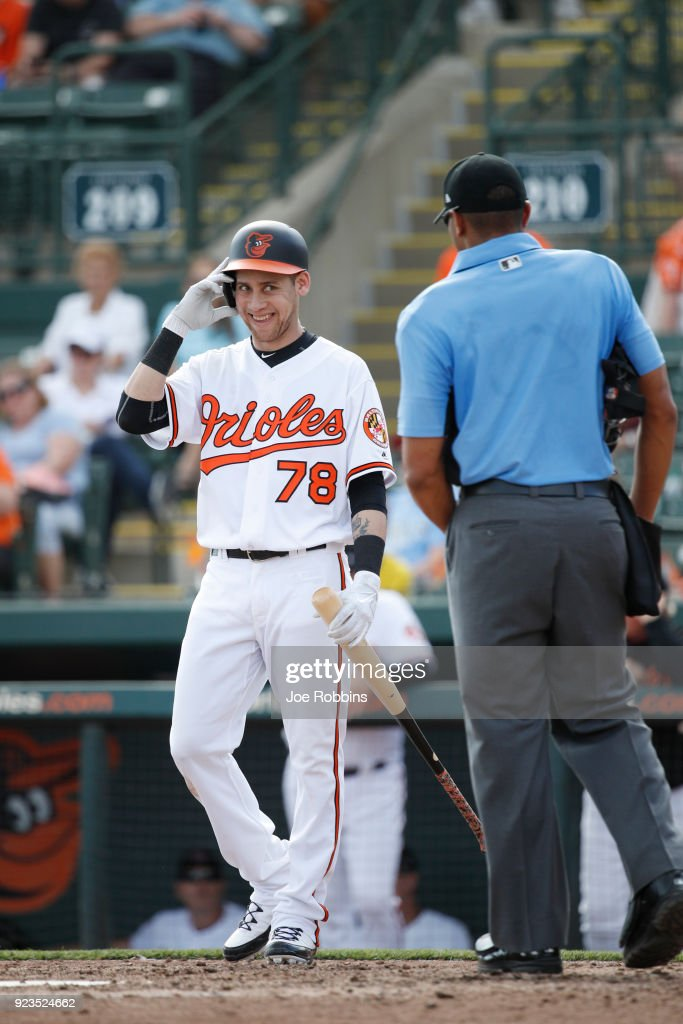 Erick Salcedo #78 of the Baltimore Orioles jokes with umpire Jeremie Rehak while stepping in to bat against the Tampa Bay Rays during a Grapefruit League spring training game at Ed Smith Stadium on February 23, 2018 in Sarasota, Florida. The Rays won 6-3.