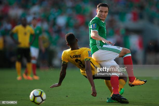 Erick Torres of Mexico and Damion Lowe of Jamaica compete for the ball during a match between Mexico and Jamaica as part of CONCACAF Gold Cup...