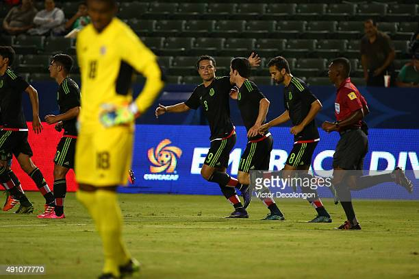 Erick Torres of the Mexico congratulates teammate Marco Bueno after Bueno's goal in the first half as goalkeeper Darryl Parker of Costa Rica looks on...