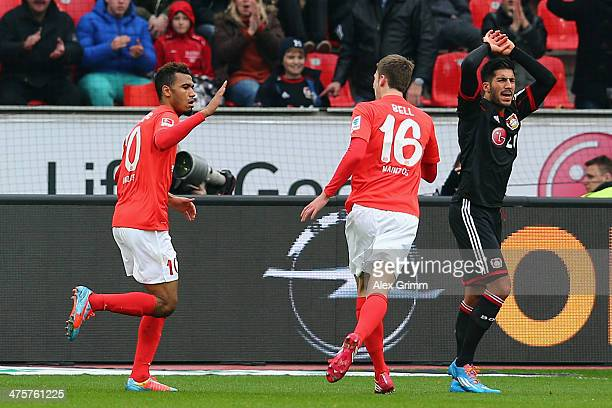 EricMaxim ChoupoMoting of Mainz celebrates his team's first goal with team mate Stefan Bell as Emre Can of Leverkusen reacts during the Bundesliga...