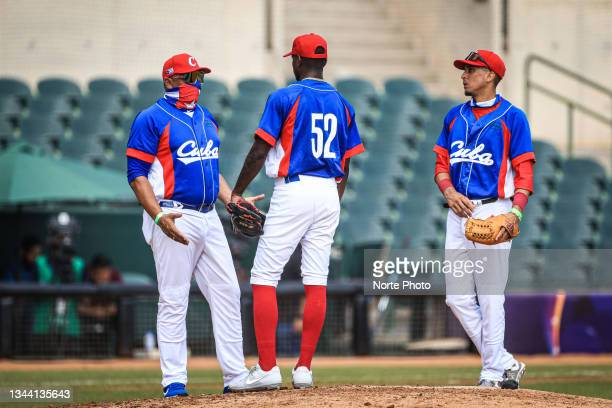Eriel Sanchez Coach of Cuba meets with pitcherJonathan Carbo and Miguel Gonzalez in the third inning during the game between Colombia and Cuba at...