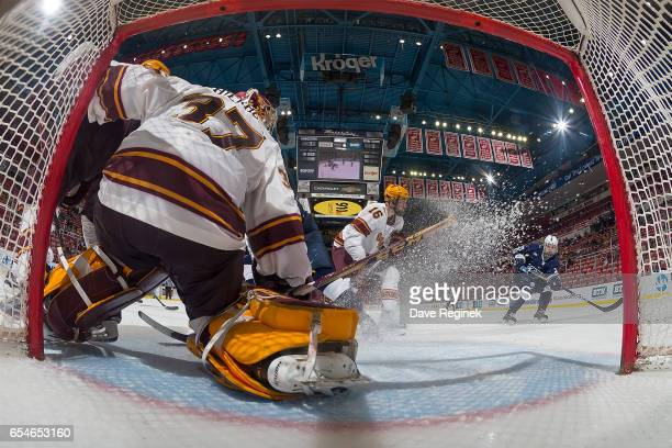 Erik Autio of the Penn State Nittany Lions scores the game winning second OT goal on Eric Schierhorn of the Minnesota Golden Gophers during game two...