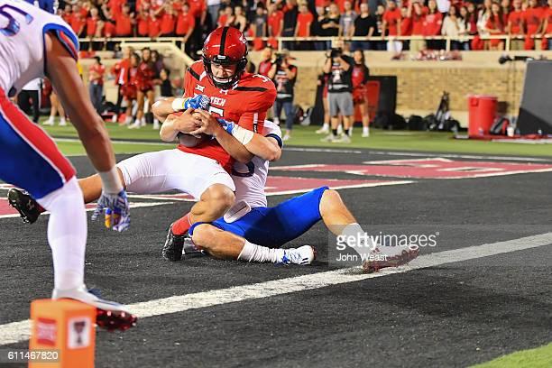 Erik Baughman of the Texas Tech Red Raiders is tackled in the end zone for a safety by Ryan Schadler of the Kansas Jayhawks during the first half on...