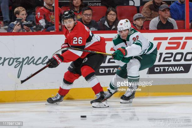 Erik Brannstrom of the Ottawa Senators passes the puck against Kevin Fiala of the Minnesota Wild at Canadian Tire Centre on October 14 2019 in Ottawa...