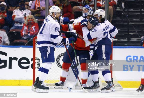 Erik Cernak and Ryan McDonagh of the Tampa Bay Lightning moves Gustav Forsling of the Florida Panthers from the crease during the first period in...