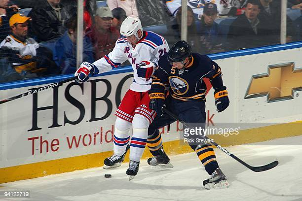 Erik Christensen of the New York Rangers battles for the puck against Toni Lydman of the Buffalo Sabres during the game at HSBC Arena on December 5...