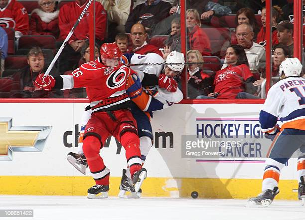 Erik Cole of the Carolina Hurricanes battles along the boards with Matt Moulson of the New York Islanders during a NHL game against on November 3,...