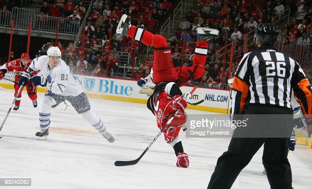 Erik Cole of the Carolina Hurricanes gets upended by Ian White of the Toronto Maple Leafs during a NHL game on November 15, 2009 at RBC Center in...