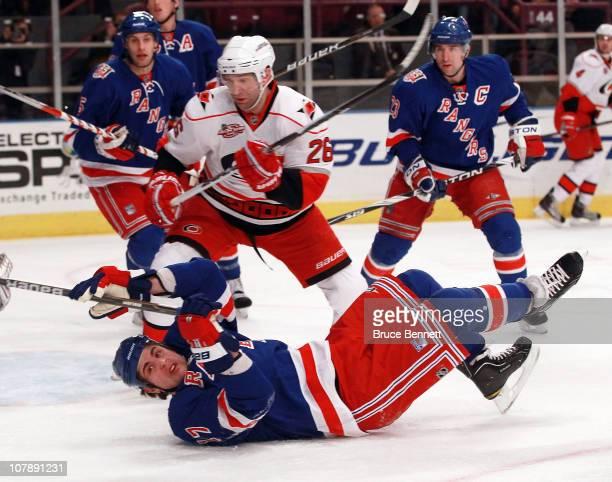 Erik Cole of the Carolina Hurricanes knocks down Matt Gilroy of the New York Rangers at Madison Square Garden on January 5, 2011 in New York City.
