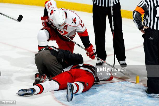 Erik Cole of the Carolina Hurricanes lies injured face down on the ice as teammate Eric Staal watches against the Florida Panthers at the Bank...