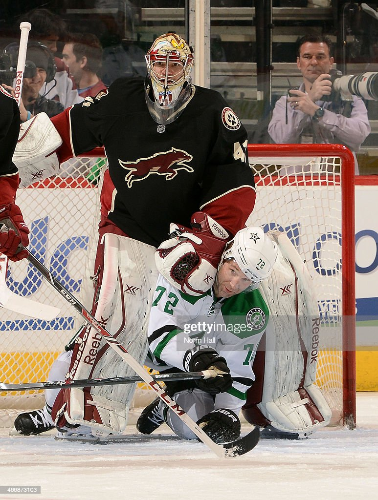 Erik Cole #72 of the Dallas Stars and goaltender Mike Smith #41 of the Phoenix Coyotes get tangled in front of the net during the second period at Jobing.com Arena on February 4, 2014 in Glendale, Arizona.