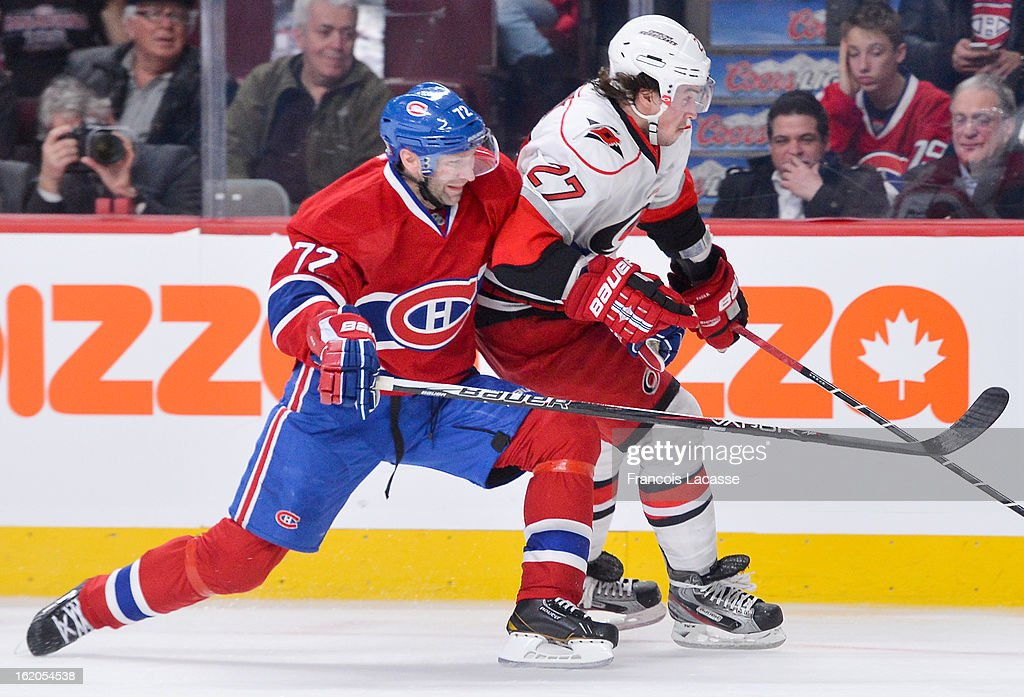 Erik Cole #72 of the Montreal Canadiens attempts to tie up Justin Faulk #27 of the Carolina Hurricanes during the NHL game on February 18, 2013 at the Bell Centre in Montreal, Quebec, Canada.