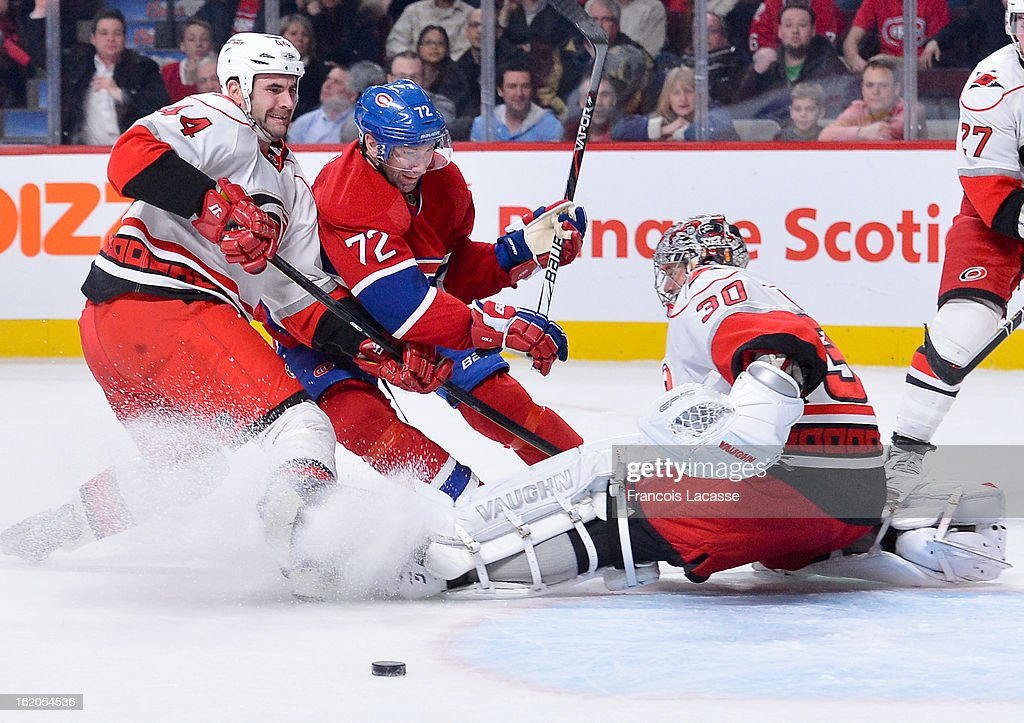 Erik Cole #72 of the Montreal Canadiens gets tied up by Jay Harrison #44 of the Carolina Hurricanes as the puck slides past goalie Cam Ward #30 during the NHL game on February 18, 2013 at the Bell Centre in Montreal, Quebec, Canada.
