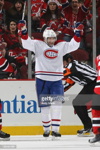 Erik Cole of the Montreal Canadiens raises his arms in celebration of his game winning goal against the New Jersey Devils during the game at the...