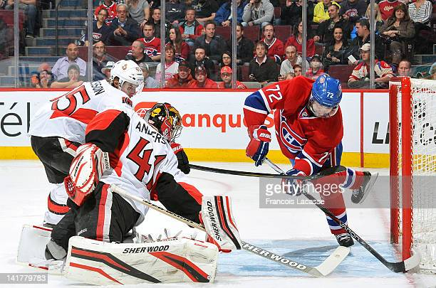 Erik Cole of the Montreal Canadiens slides the puck in the net behind goaltender Craig Anderson the Ottawa Senators during the NHL game on March 23,...