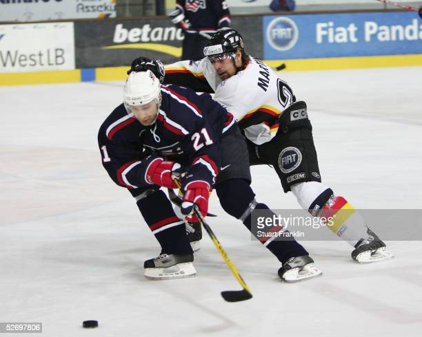 Erik Cole of USA tussles with Thomas Martinec of Germany during The International Friendly Ice Hockey match between Germany and USA at The Olympic...