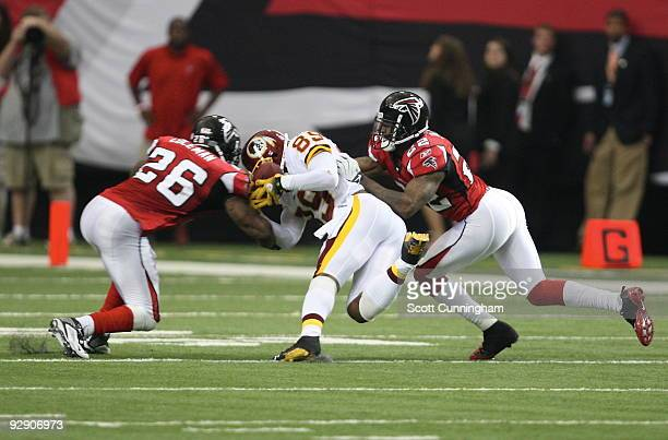 Erik Coleman and Chevis Jackson of the Atlanta Falcons knock the ball loose from Santana Moss of the Washington Redskins at the Georgia Dome on...