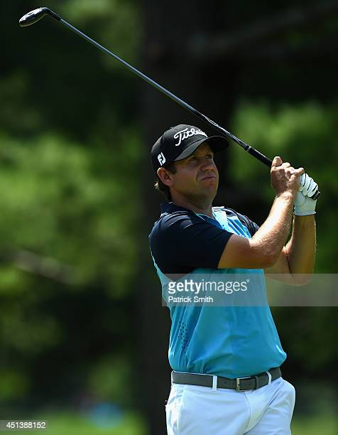 Erik Compton of the United States watches his tee shot on the second hole during the third round of the Quicken Loans National at Congressional...