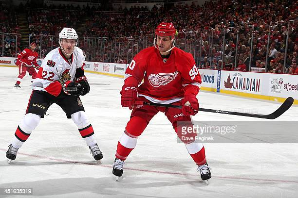 Erik Condra of the Ottawa Senators and Stephen Weiss of the Detroit Red Wings glide behind the net for the puck during an NHL game at Joe Louis Arena...
